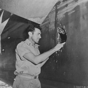 1Lt Louis Zamperini, bombardier of this B-24D Liberator 'Superman' peering through a hole in the aircraft from a 20mm shell over Nauru, Apr 20 1943; photo taken at Funafuti, Gilbert Islands. Source: National Archives